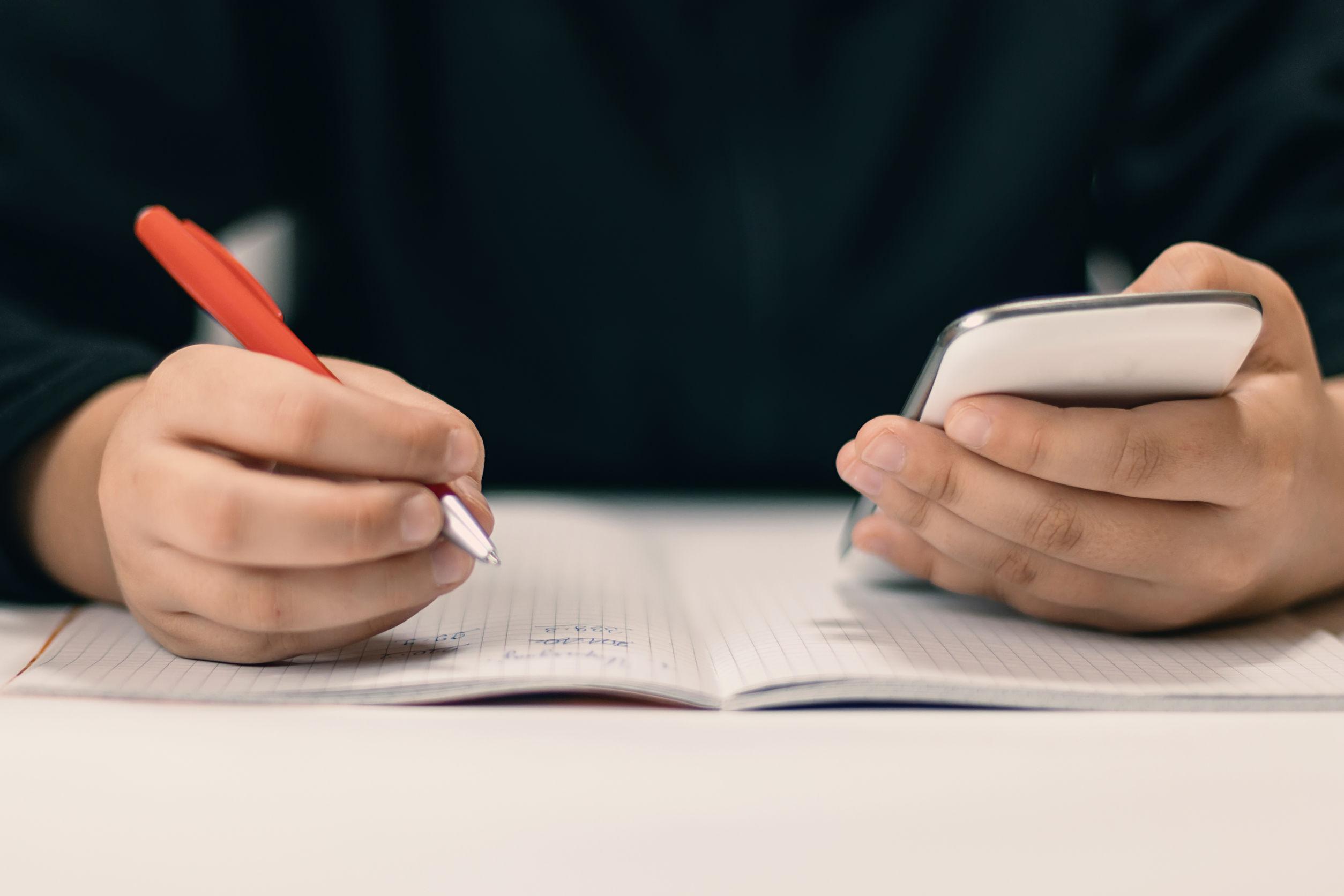 Chico escribiendo con móvil y bolígrafo.
